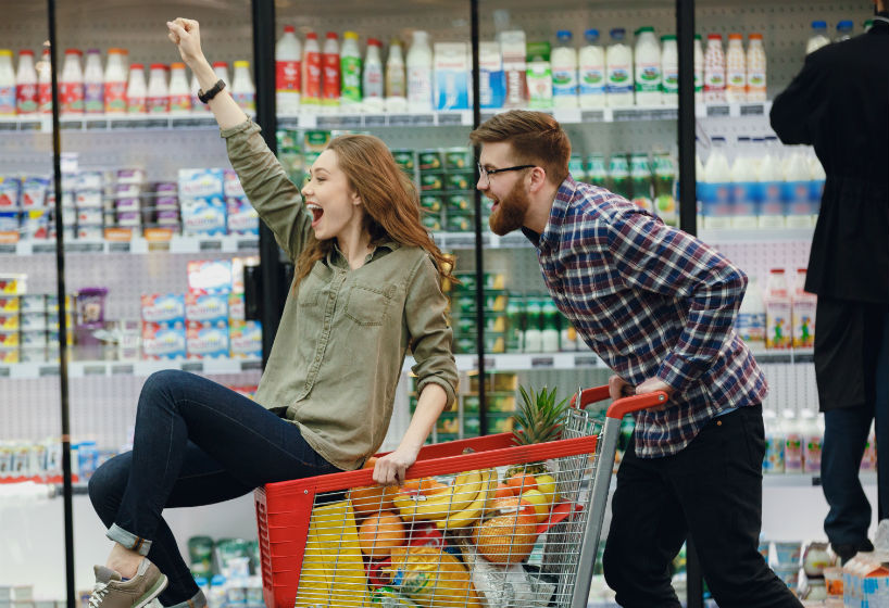 Happy couple having fun while choosing food in the supermarket
