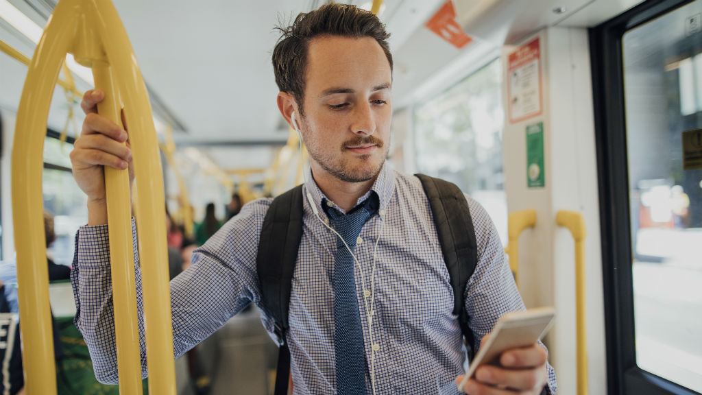 Millennial businessman is commuting on a tram in Melbourne, Victoria